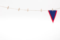 Red and blue pennant hanging on clothesline. Isolated on white background royalty free stock image