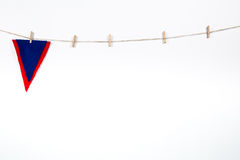Red and blue pennant hanging on clothesline. Isolated on white background stock image