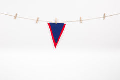 Red and blue pennant hanging on clothesline. Isolated on white background stock photo