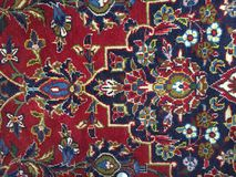Red blue Persian rug on the floor with various shapes. Square, triangle, leaf, light blue, dark blue stock photos