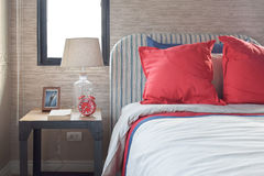 Red and blue pillows on the cozy bed with striped headboard Stock Photography