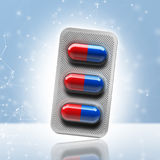 Red and blue pills in a blister on bokeh background. 3d rendering Stock Photos