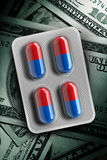 Red and blue pills in a blister on dollar bill background. 3d rendering Royalty Free Stock Images