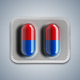 Red and blue pills in a blister on gray background. 3d rendering Stock Images