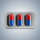 Red and blue pills in a blister on gray background. 3d rendering Stock Photos
