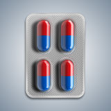 Red and blue pills in a blister on gray background Stock Photo