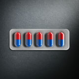 Red and blue pills in a blister on gray background. 3d rendering Royalty Free Stock Images