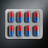 Red and blue pills in a blister on gray background. 3d rendering Royalty Free Stock Image