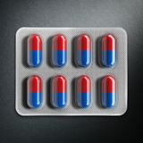 Red and blue pills in a blister on gray background. 3d rendering Stock Image