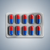 Red and blue pills in a blister on gray background. 3d rendering Royalty Free Stock Photography