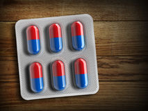Red and blue pills in a blister on a wooden background. 3d rendering Stock Image