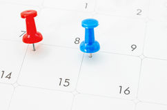 Red and blue pin on White Calendar. Royalty Free Stock Images