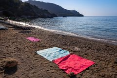 The red, blue and pink towels are laid out in an empty gravel beach in a heavenly bay. Sea and sky background royalty free stock photo