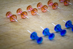Red and blue pins against each other on a wooden table Royalty Free Stock Photos