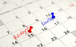 Red and blue pins marking the important days on a calendar Stock Photo