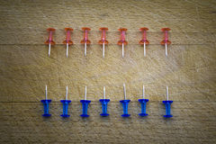 Red and blue pins on a wooden table Stock Image