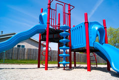 Red and Blue Playground Park Structure. A red and blue playground with a slides and climbing structures Stock Photos