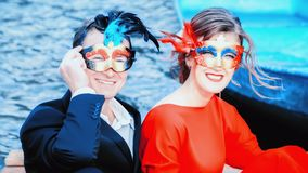 Happy Man And Woman In Masquerade Masks. Red and blue portrait of a happy young couple in masquerade masks - elegantly dressed men and women laughing against the royalty free stock photo