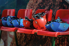 Red and blue protective helmets of climbers. On red armchairs Royalty Free Stock Photos