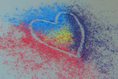 Colourful chalk dust heart outline. Red, blue, purple and yellow chalk dust make up a stunning heart shape royalty free stock photography