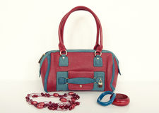 Red and blue purse with matching necklace and bracelets. Stock Photos