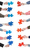 Red and blue puzzle pieces in people hands Stock Images