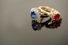 Red and blue sapphire rings in diamond settings Stock Image