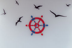 Red blue ship's steering wheel and flying birds -  illustration on wall Stock Images