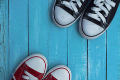 Red and blue sneakers, top view. Red and blue sneakers on a blue wooden background, top view Royalty Free Stock Images