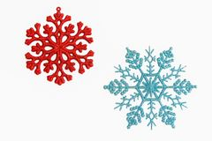 Red and blue snowflake ornaments. Red and blue sparkly snowflake ornaments on a white background Royalty Free Stock Image