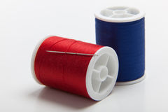 Red and blue spools of sewing thread Stock Photography