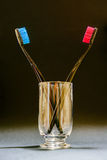 Red and blue teeth brushes in a glass on black background. Royalty Free Stock Image