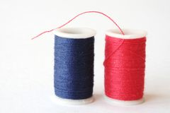 Red and Blue Thread. Spools of red and blue thread on an off-white background Royalty Free Stock Photos