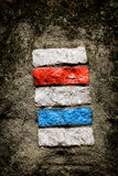 Red and blue tourist track signs on the rock Royalty Free Stock Photo