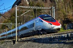 Red blue train in motion alps mountains. High speed mountain train arrives at Switzerland. Train station in mountains royalty free stock images