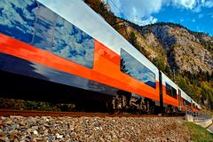 Red blue train in motion in Austrian alps mountains. High speed mountain train arrives at Hallstatt Obertraun train station. In mountains. Location: resort royalty free stock photography
