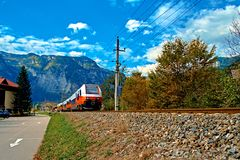 Red blue train in motion in Austrian alps mountains. High speed mountain train arrives at Hallstatt Obertraun train station. In mountains. Location: resort stock photo