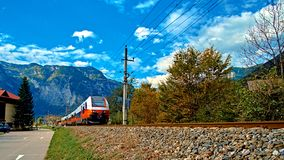 Red blue train in motion in Austrian alps mountains. High speed mountain train arrives at Hallstatt Obertraun train station. In mountains. Location: resort royalty free stock image