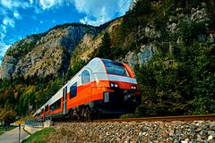 Red blue train in motion in Austrian alps mountains. High speed mountain train arrives at Hallstatt Obertraun train station. In mountains. Location: resort royalty free stock images