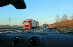 Red and blue truck drives on the European highway D1 at sunset or sunrise. royalty free stock image