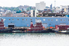 Red and Blue Tugboats by Blue Building Stock Photo