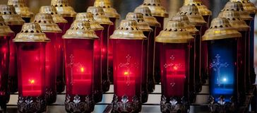 Red and blue votive candles in church Stock Photos