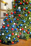 Red, blue and white decorating balls on the christmas tree at th Royalty Free Stock Images