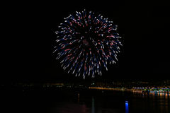 Red, blue, white fireworks. In black night sky over the river Stock Images