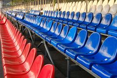 Red, blue and white sports stadium seats. Empty stands, no spectators at the competitions royalty free stock photography