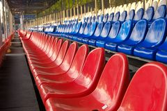Red, blue and white sports stadium seats. Empty stands, no spectators at the competitions stock photography
