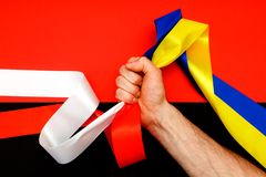 Red blue white yellow black conflict between Ukraine Poland two flag top view hand right sector confrontation. The man`s hand clamps in the fist the symbols of Stock Photos