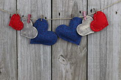 Red, blue and wood country hearts hanging on clothesline with wooden background Royalty Free Stock Image