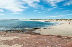 Red Bluff Beach: Coral Coast. KALBARRI,WA,AUSTRALIA-APRIL 22,2016: Tourists walking the Red Bluff beach with the Indian Ocean seascape and sandstone rock under a Royalty Free Stock Photo