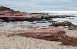Red Bluff Inlet. Rugged beach landscape with red sandstone rock, Indian Ocean inlet and sandy beach at Red Bluff under a blue sky with clouds on the coral coast Stock Photos